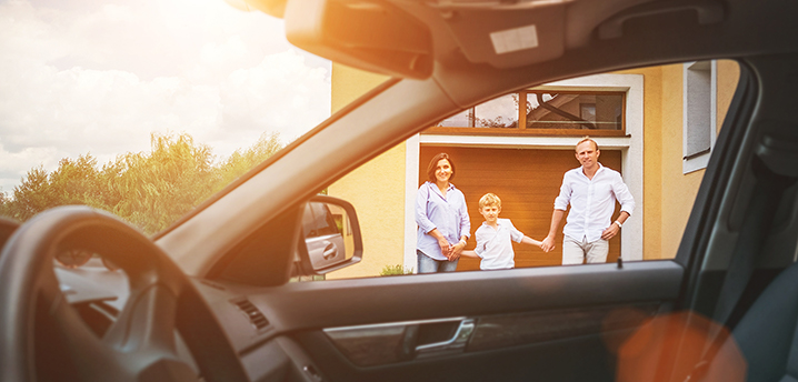 family standing outside home and car - refinancing car loan or mortgage first