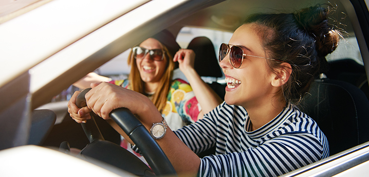 two young women driving and laughing- how to save money on car insurance